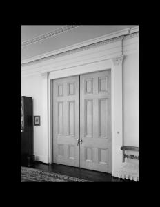 Interior of greek revival style room featuring hardwood floors, door mouldings, and interior cornice mouldings.