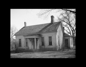 Small greek revival style house featuring steps leading to the doorway, covered porch above doorway, and window mouldings.