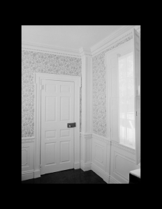 Interior of greek revival style house featuring door mouldings, columns, interior cornice and wall mouldings.