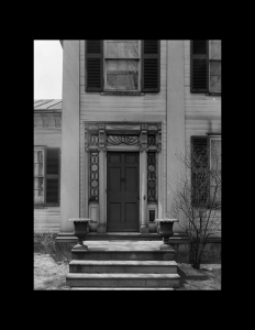 Greek Revival Western Reserve style building featuring double hanging windows with shutters, door mouldings, and stone steps leading to entrance.
