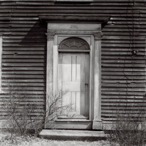 Baldwin house doorway featuring mouldings, step, and shingle siding on the house.