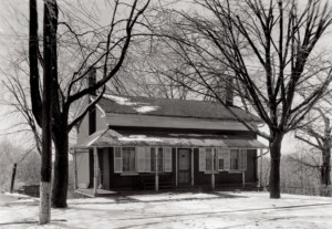Birthplace of Thomas Edison house with covered front porch, door mouldings, window mouldings with shutters, and overhanging roof.
