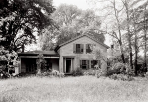 Exterior of Blackman house showcasing windows with shutters in the front, a side covered porch with no columns, and shingles for siding.
