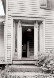 Front door of the Blackman house featuring steps to entrance, beautiful door mouldings, and window casing along the side of the door.
