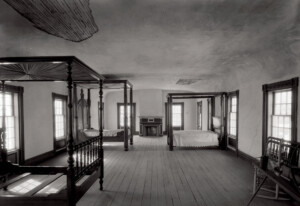Interior of Columbian House bedroom showing off hardwood floors, brick fireplace, and window casing mouldings.
