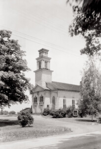 Exterior of congressional church building featuring a large centered tower on roof, shingle siding, and window mouldings with shutters.