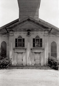 Exterior of congressional church building showcasing large doorway to entrance, featuring steps to entrance and window casing with shutters.