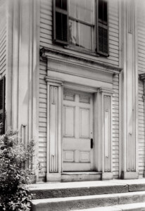 Exterior entrance door to the congressional church building, the door features columns, panel molds, and shingle siding around the door.