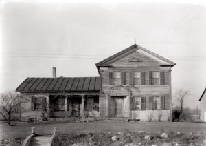 Exterior of Dirlam Allen House featuring covered porch with columns, windows casings with shutters, and door mouldings with panel molds.