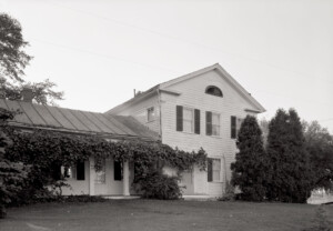Updated exterior of Dirlam Allen House featuring covered porch with columns, windows casings with shutters, all painted in white.