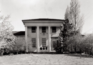 Exterior of Fay Homestead House featuring large pillars with a covered front porch, three main entrances, and center of house towers over sides.