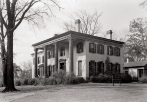 Exterior of Frederick Kinsman House featuring tall windows with shutters, covered front porch with columns, side steps, and door mouldings.