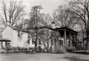 Exterior of Frederick Kinsman House featuring tall windows with shutters, and covered front porch with columns.