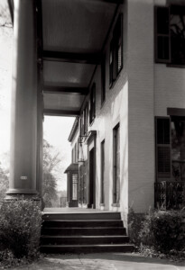 Exterior of Frederick Kinsman House featuring steps to entrance, covered porch, and door mouldings.