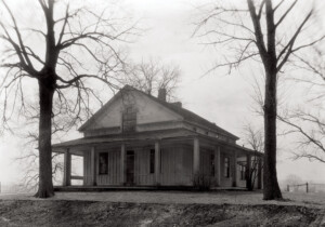 Exterior of Freer house featuring different geometrically shaped windows, windows with shutters, wrap around covered porch, and door panel molds.