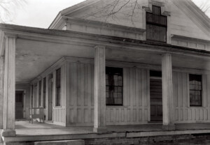 Close up of Freer house exterior showcasing covered wrap around porch along with columns and exterior cornice mouldings.