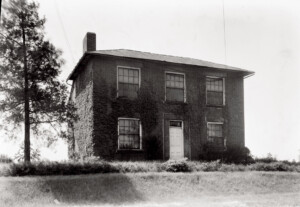 Exterior of Hardwick House featuring double windows, all brick exterior, stone foundation, and front doorway with door panel molds.
