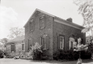 Exterior of Hopwood House featuring brick wall, window casing with shutters, and door casing with window casing and panel molds.