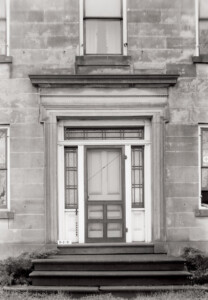 Exterior of Hurst House main doorway featuring window casing, steps to entrance, and column detail.