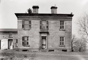 Exterior of Hurst House showcasing all brick walls, steps to entrance, door casing with window casing and windows with shutters.