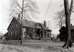 Exterior of Iddings House featuring windows with shutters, and front door with panel molds, and two chimneys.