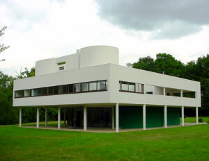 International style building that is rectilinear, asymmetrical, white and has a covered ground level with open spaces divided by columns.