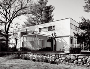 White rectangular international style house that has a covered entrance walkway with glass walls, and side window mouldings.
