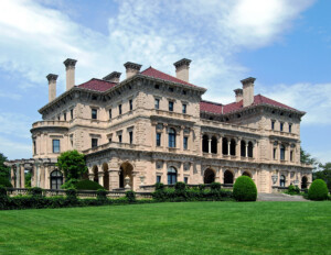 Four story italian renaissance style castle featuring many chimneys, balconies, columns, cornice mouldings, and a low pitched hipped roof.
