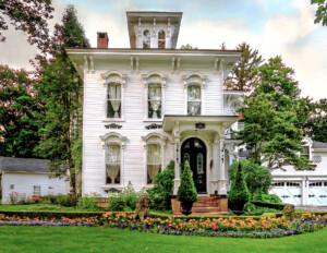 Cottage like italianate style home with a covered porch with columns and steps accompanied with beautiful window mouldings, and door mouldings.