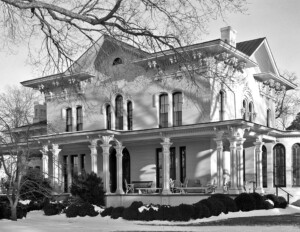 Italianate style house with hipped roof, beautiful cornice mouldings, tall windows, and a covered front porch with columns.