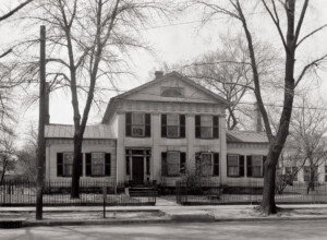 Exterior of John Mathews House with windows with shutters, large columns in front, stairway to front door, and doorway mouldings with column detail.