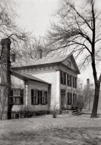 Side view of John Mathews House with windows with shutters, large columns in front, exterior cornices, and doorway mouldings with column detail.