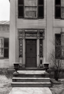 Exterior of John Mathews House front door with casing mouldings, and steps leading to entrance.