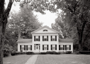 Exterior of John Mathews House with windows with shutters, large columns in front, exterior cornices, and doorway mouldings with column detail.