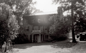 Exterior of Jonathan Hale House featuring windows with shutters, covered front porch, and doorway casing with panel molds.
