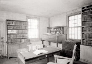 Interior of Joshua R Giddings law office featuring window casing, doorway casing, office desks, and library book storage.