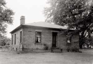 Exterior of Lewis House featuring all brick walls, door casing mouldings, and two chimneys.