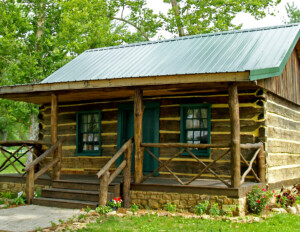 Log Cabin Style house with handcrafted logs, window mouldings, door mouldings, hangover roof, front covered porch with steps for entrance.