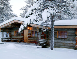 Log Cabin Style house in winter, traditional logs, hangover roof, and window mouldings.