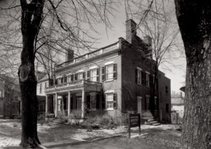 Exterior of Martin House featuring windows with shutters, door casing with column detail, covered porch with columns, and balustrades on roof.