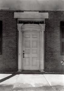 Exterior of Martin House doorway featuring column details, panel molds, window casing, and stylish door knob.
