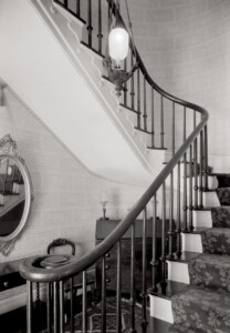 Interior of Martin House featuring staircase with newel post, stair treads, stair balusters, and decorative ornaments.