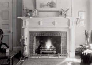 Interior of Martin House fireplace mantel featuring mantel mouldings, column detail, and an all brick fireplace interior.