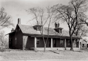 Exterior of Matt Gray House featuring a covered porch, doors with panel molds, dormers on roof, three chimneys, and shingle siding.