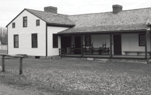 Exterior of Meriman Cook House featuring shingle siding, windows with shutters, and door casing featuring panel molds.