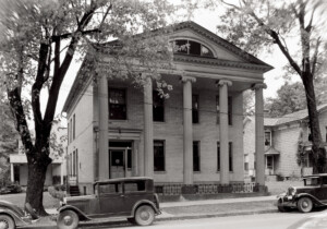 Exterior of Moore Brewster House with covered front porch with columns, exterior cornice mouldings, and window casing on roof.