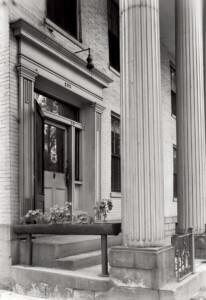 Exterior of Moore Brewster House pillar featuring front door with door casing, panel molds, window casing, and column detail.