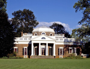 Neoclassical style home featuring large entrance way with steps, columns, and door mouldings, railing on top of roof, and tall window mouldings.