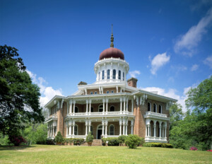 Octagonal plan style house with balconies and balustrades on both floors, steps to entrance, door mouldings, and exterior cornice mouldings.
