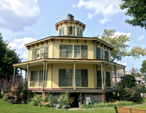 Octagonal plan style house that has wrap-around porch with window mouldings and shutters.